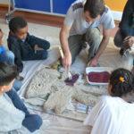Maître plasticien et élèves colorient un bas-relief