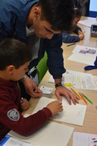 Les enfants écirivent leur lettre sous le regard des jeunes étudiants